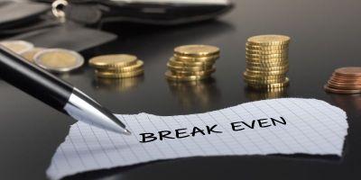break even escrito em um pedaço de papel por uma caneta. ao fundo, moedas